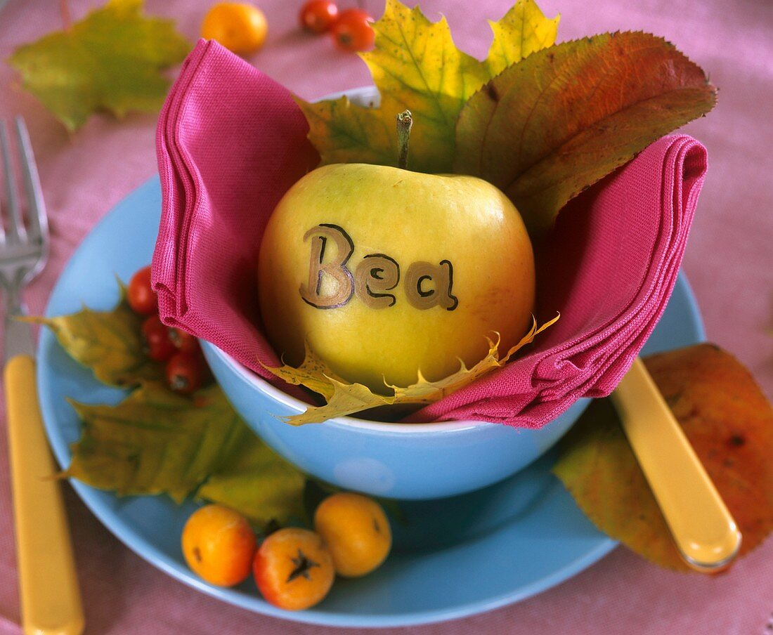 Apple place card in blue bowl, autumn leaves, crab apples