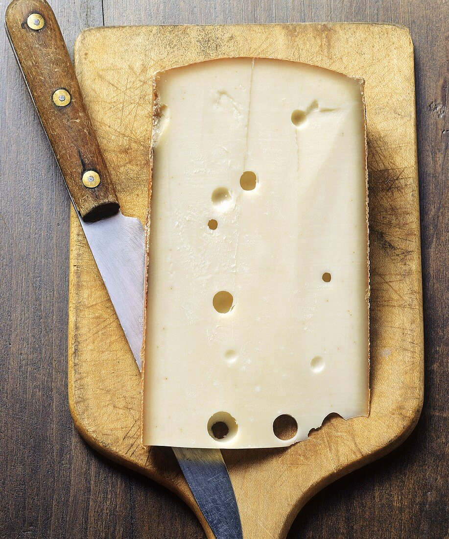 A piece of Appenzeller cheese with knife on chopping board