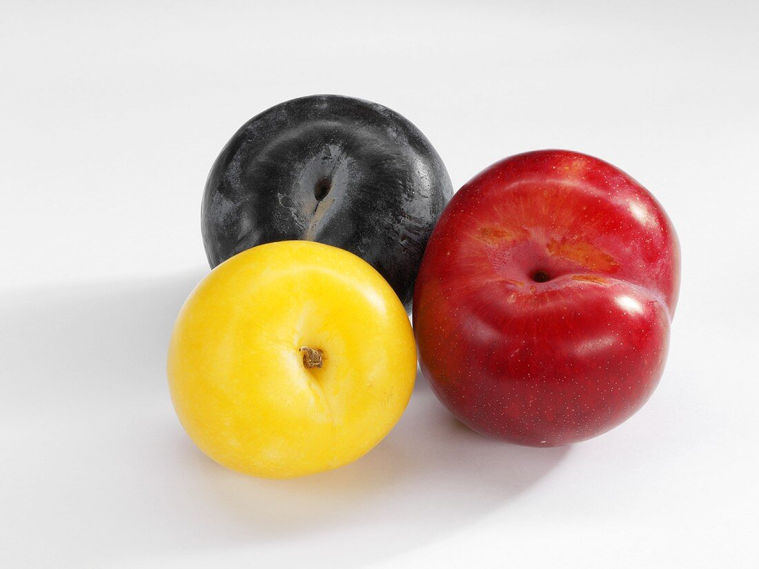 Three plums (yellow, red and black)