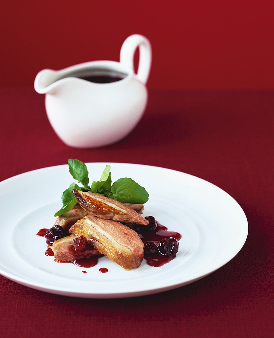 Duck breast with cherry sauce, sauce-boat in background
