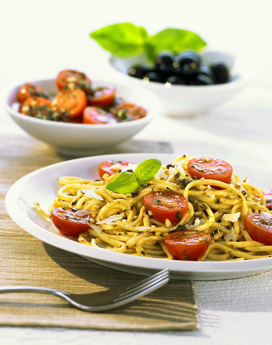 Narrow ribbon pasta with olive pesto and cocktail tomatoes