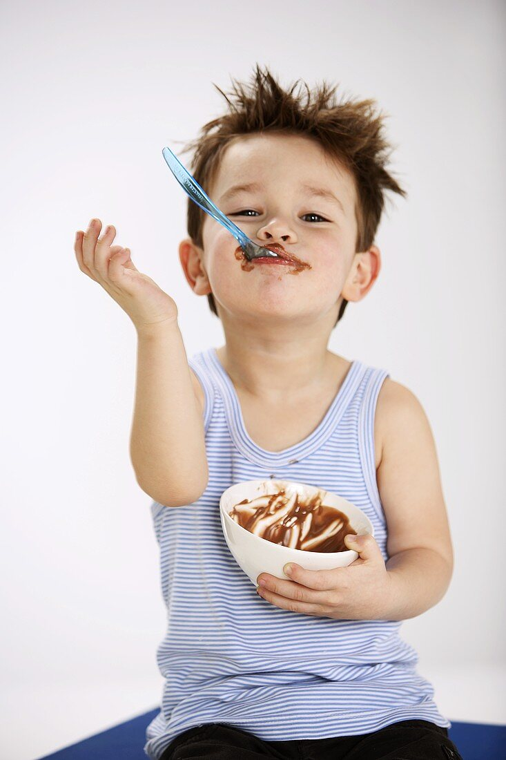 Small boy holding spoonful of chocolate pudding in his mouth