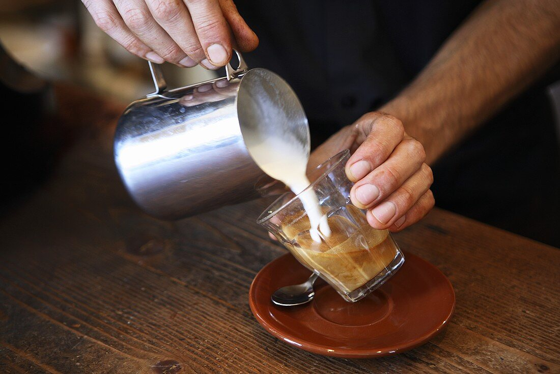 Barista pouring frothed milk into coffee