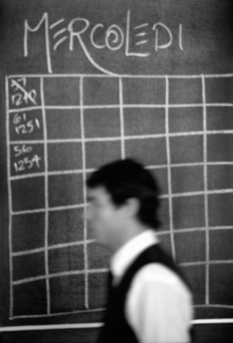 Waiter in front of blackboard