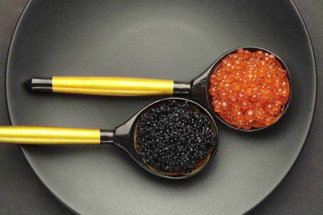Salmon caviar & sturgeon caviar in two wooden spoons (overhead view)