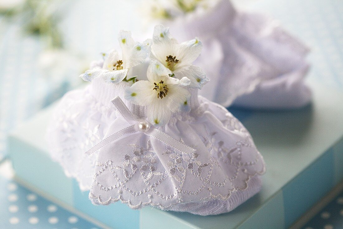 White baby shoes with delphinium flowers