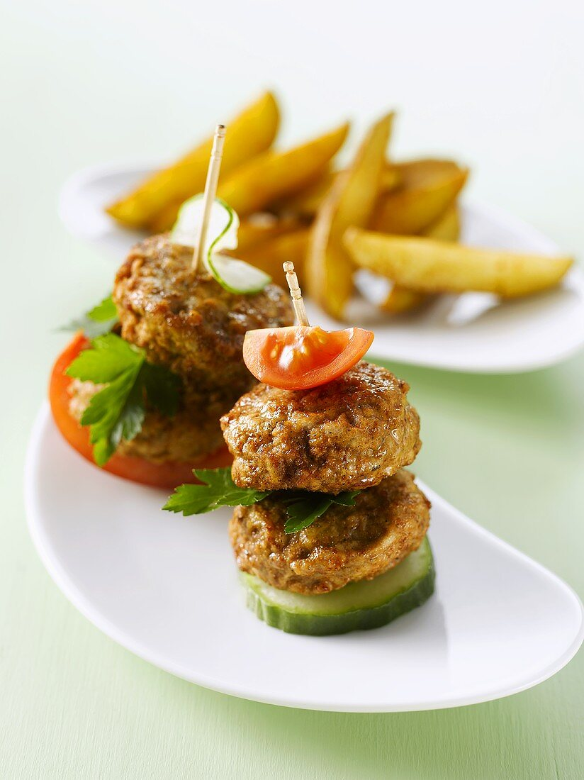 Meat patties, cucumber and tomato on cocktail sticks, potato wedges