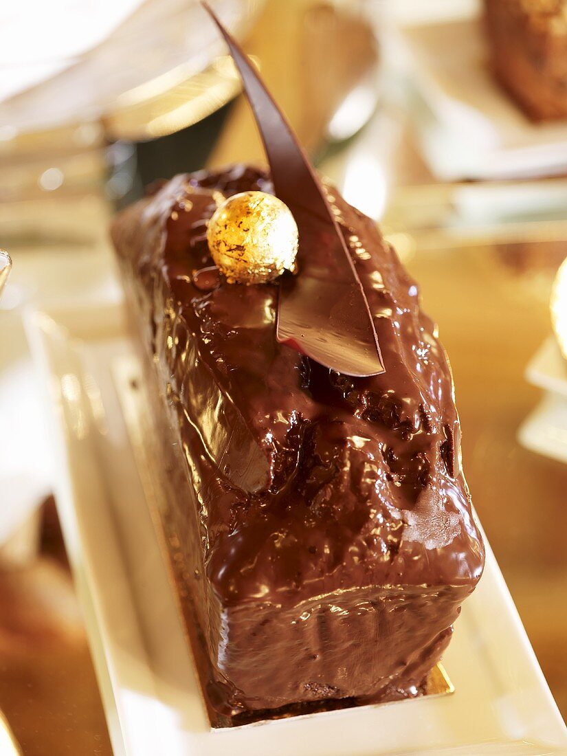 Loaf cake with shiny chocolate icing and golden ball
