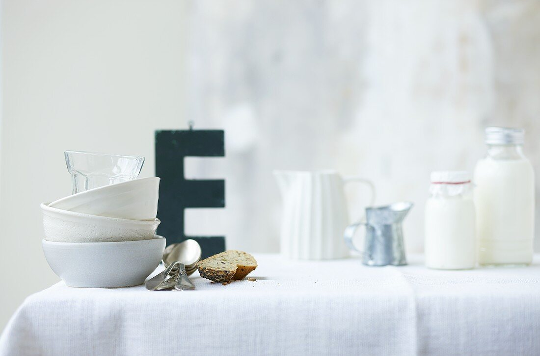 Crockery on table, letter E in background