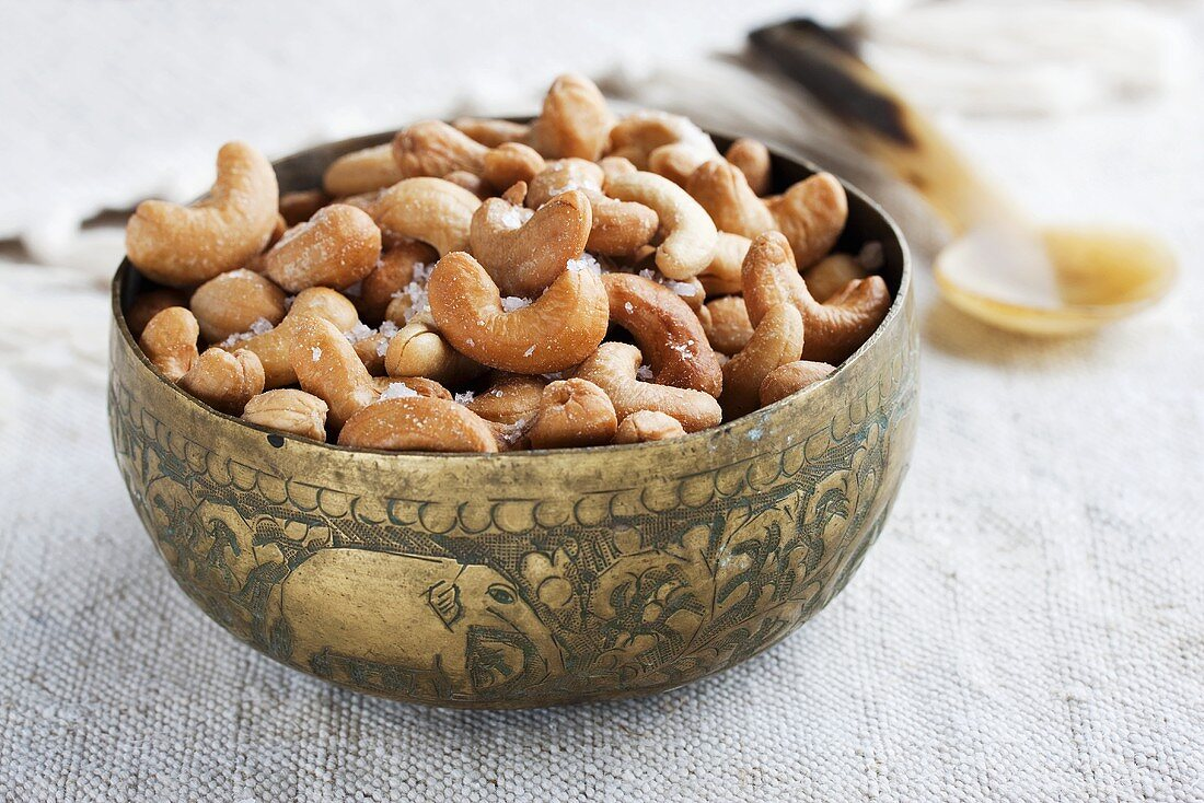 Salted cashew nuts in brass bowl