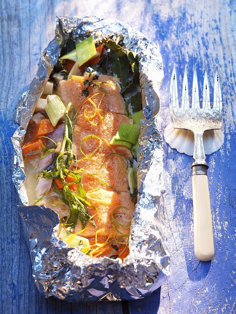 Brook charr fillets and root vegetables cooked in aluminium foil