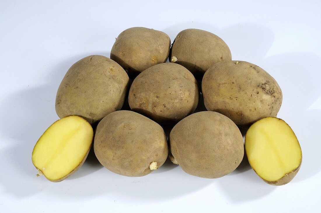 Several potatoes (variety 'Adretta'), whole and halved