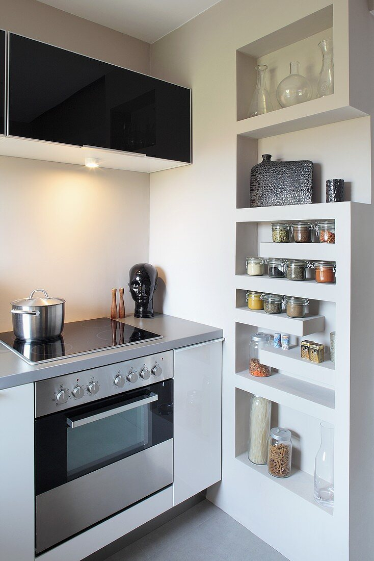 Detail of a designer kitchen with wall-mounted cupboard above ceramic hob and recessed shelving for spices
