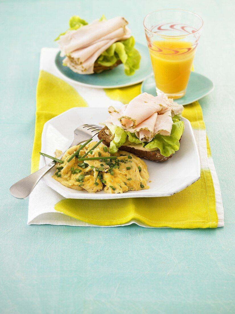 Scrambled egg and open turkey ham sandwich on pumpkin bread