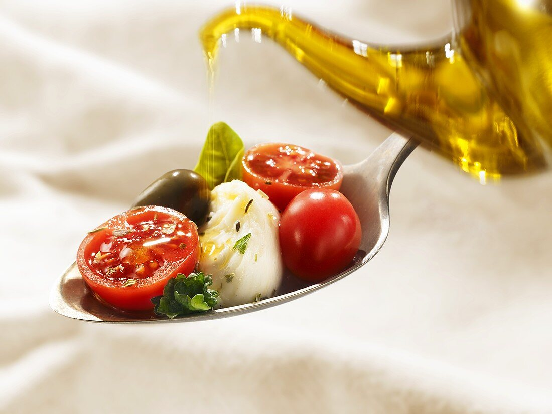 Drizzling tomatoes, mozzarella and basil with olive oil