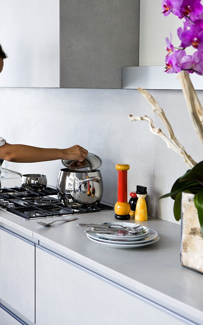 A pan on a gas hob with a hand lifting the lid