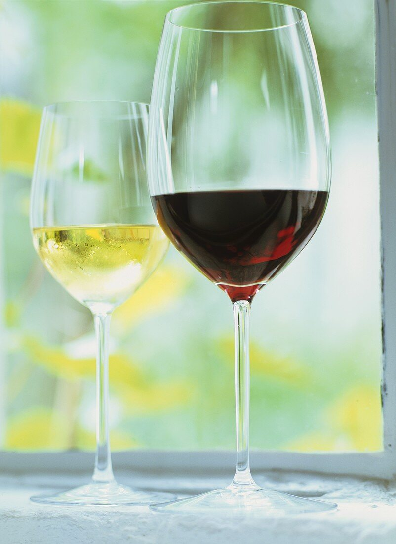 Glass of red wine in front of glass of white wine