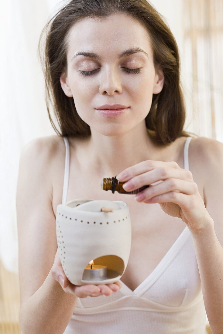 A woman drizzling scented oil in a lamp