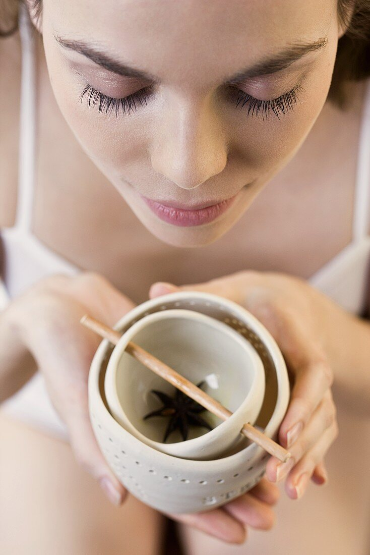A woman sniffing an oil burner