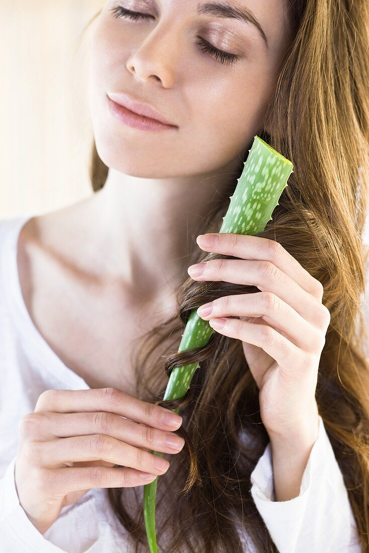 A woman wrapping her hair around an aloe vera leaf