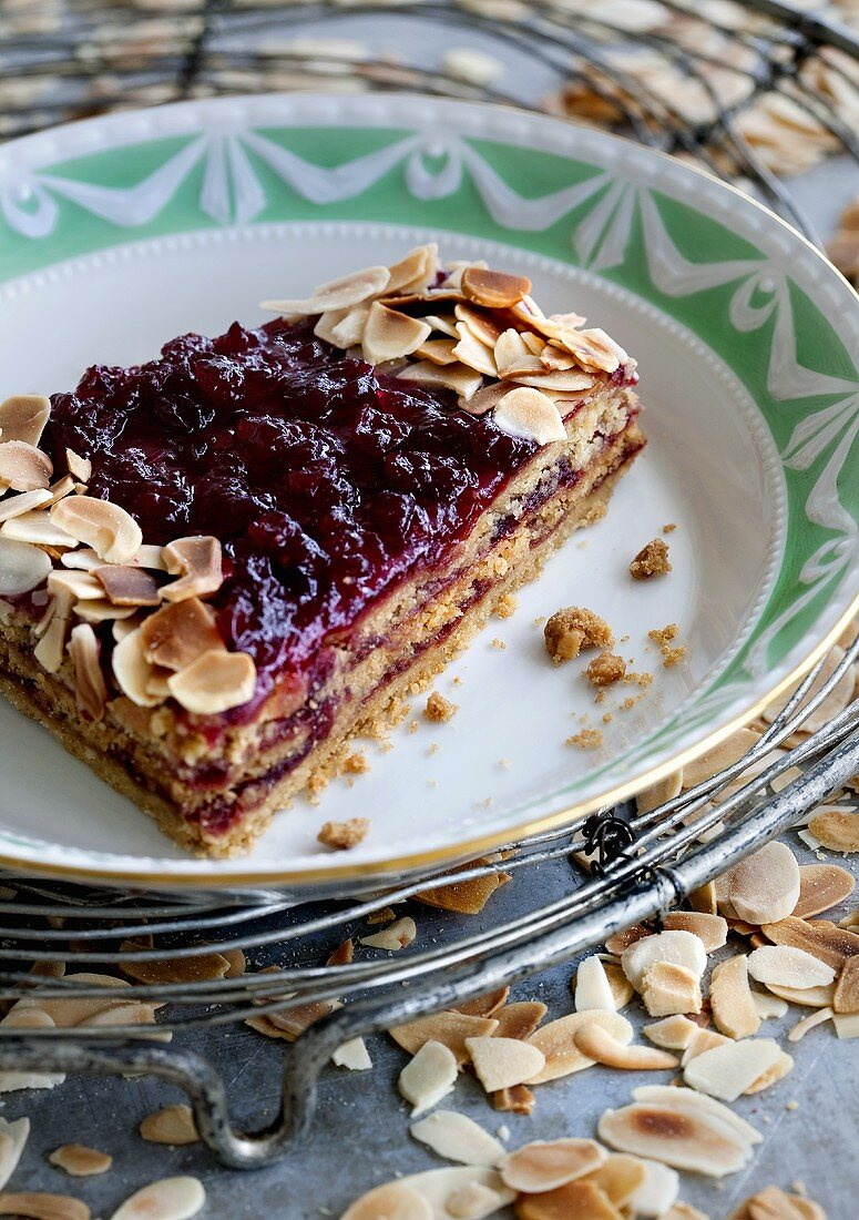A slice of Linzer tart with lingonberry jam