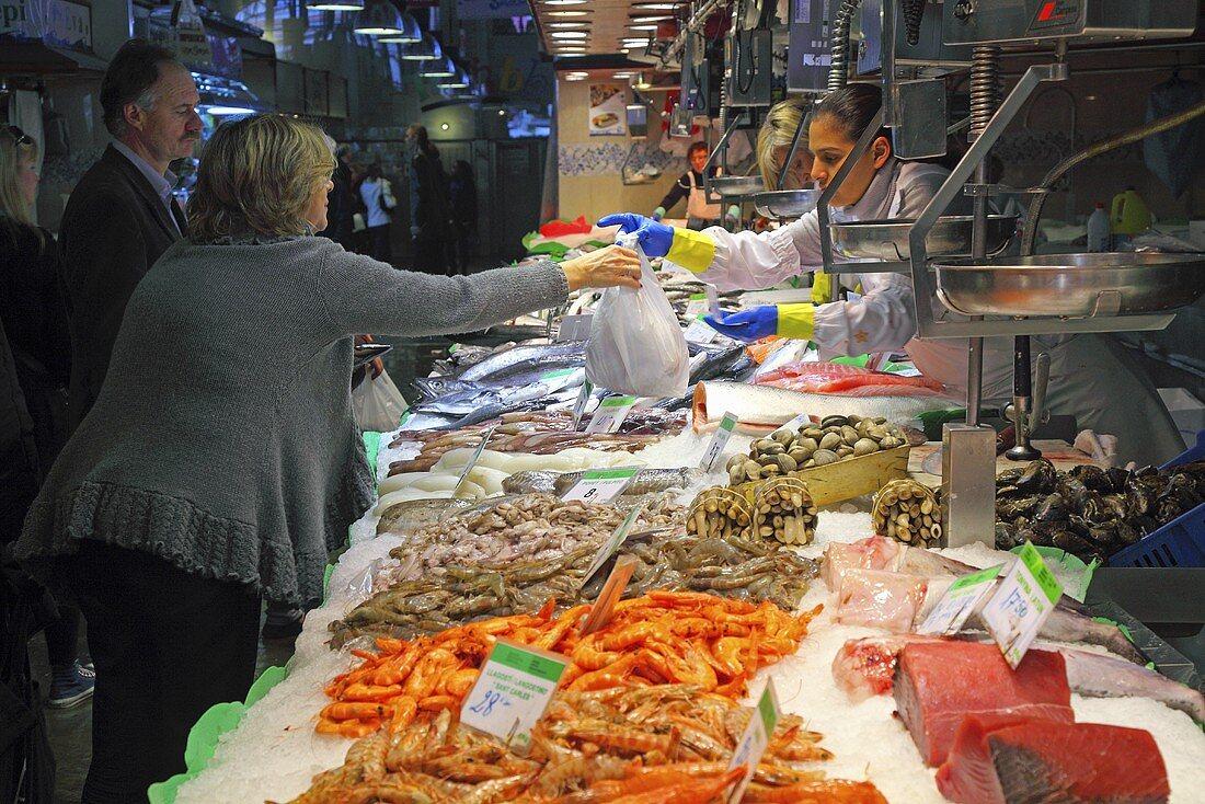 Customers at a fish and seafood market stall (Mercat de St. Josep (Boqueria), Las Ramblas, Barcelona, Spain)