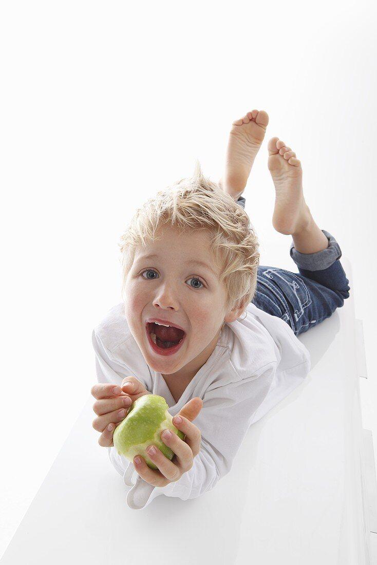 A little boy holding a half-eaten apple