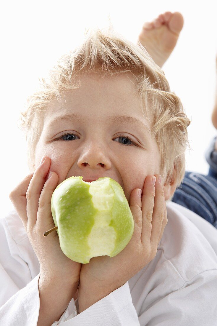 A little boy eating an apple