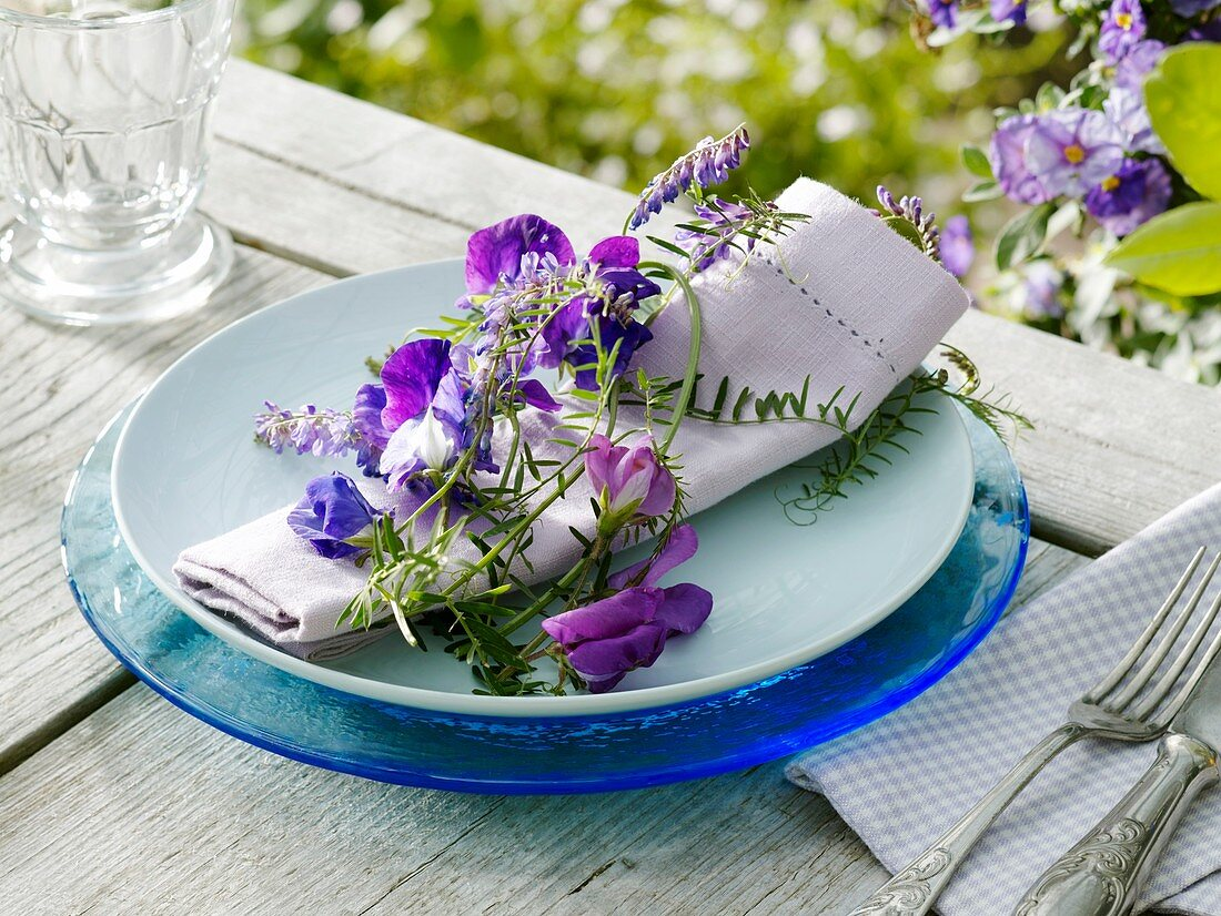 Place-setting with sweet peas and vetch on napkin