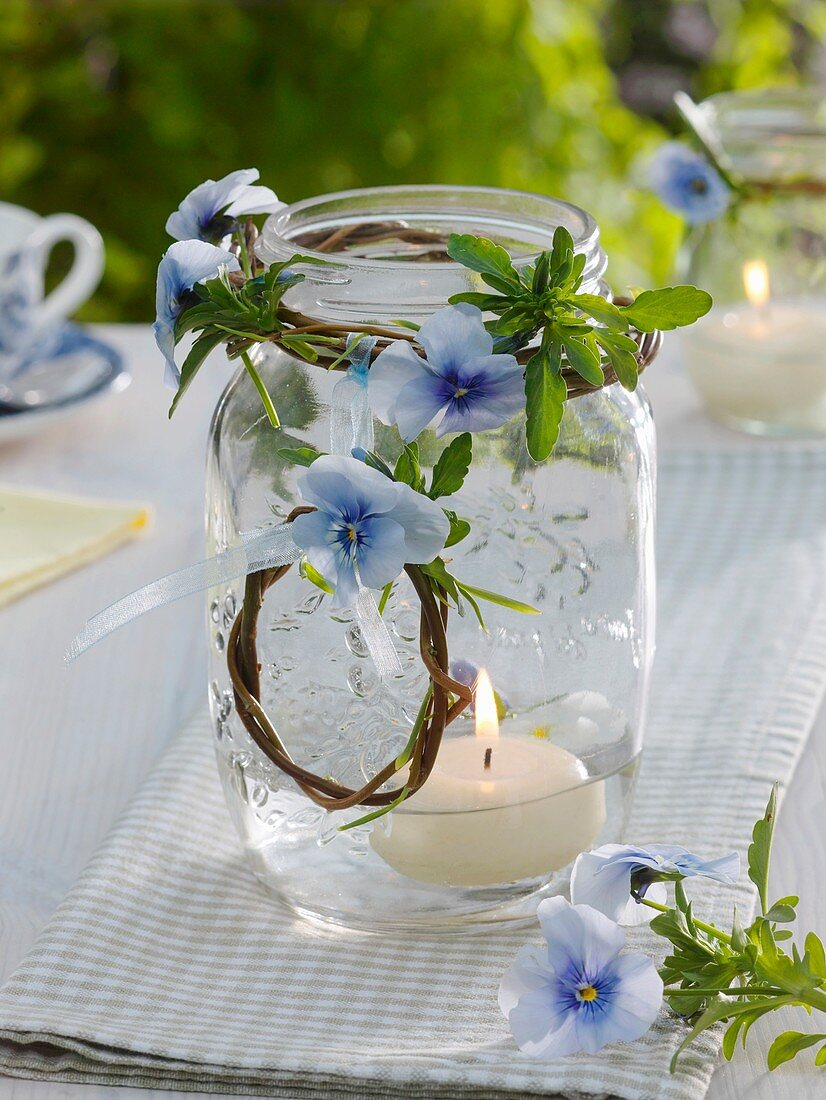Candle in jar with small willow wreath and horned violets