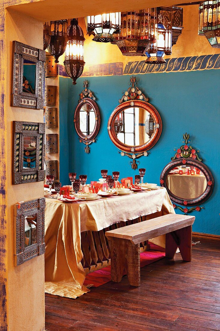 Dining room with table laid for special occasion, wall mirrors