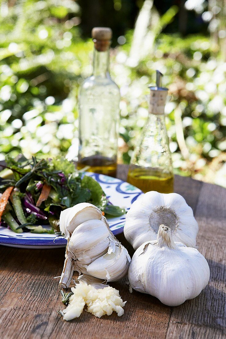 Garlic in front of plate of salad
