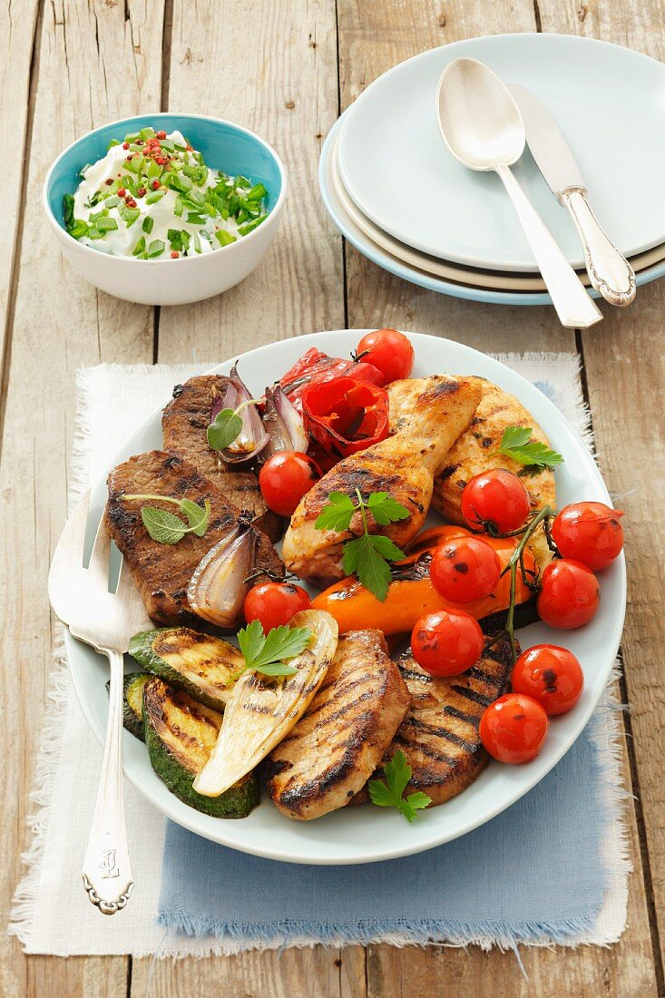Platter of barbecued chicken legs, beef, pork and vegetables