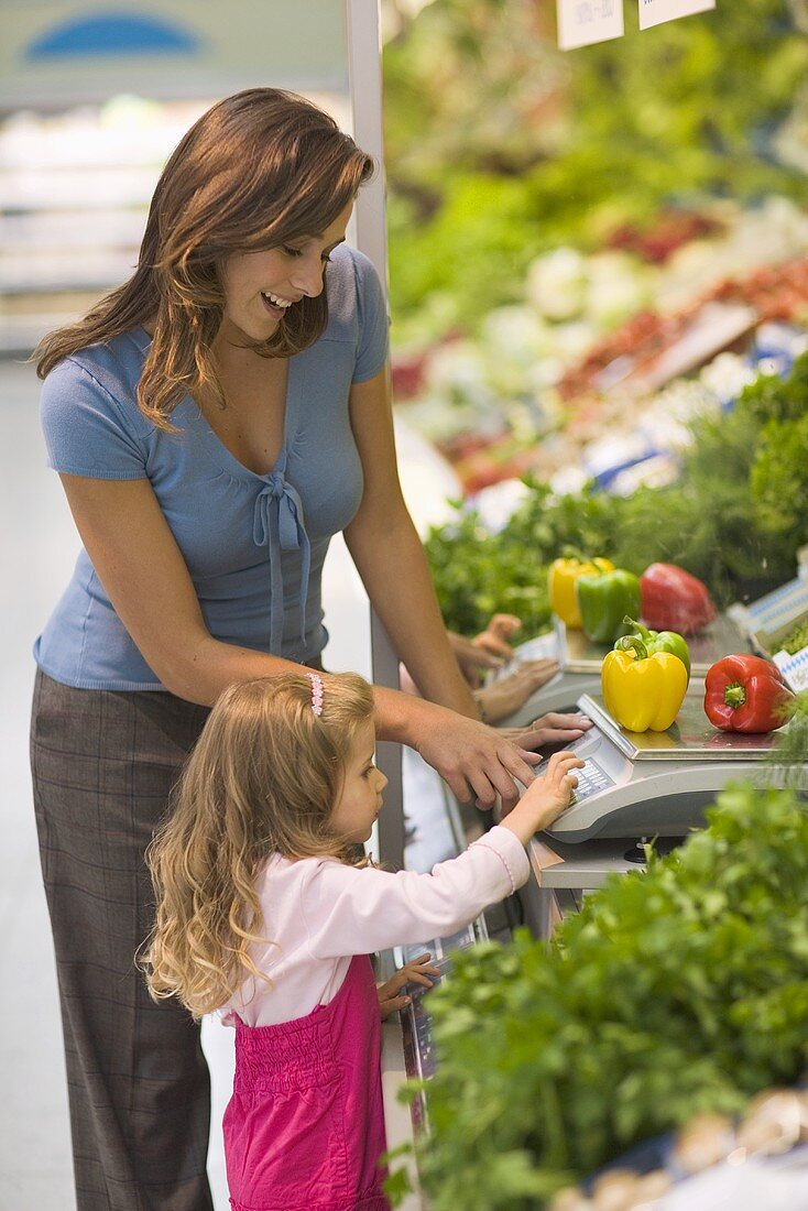 Mother and daughter weighing vegetables in a supermarket