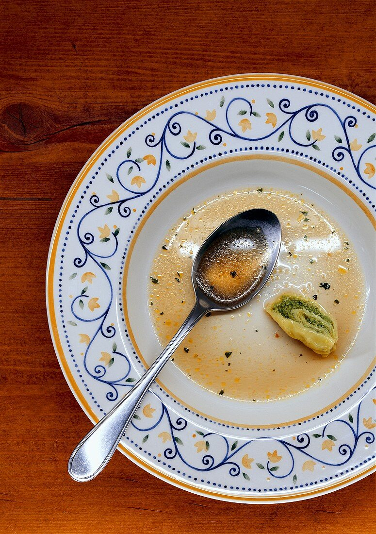 Plate of soup with pasta envelopes, half eaten