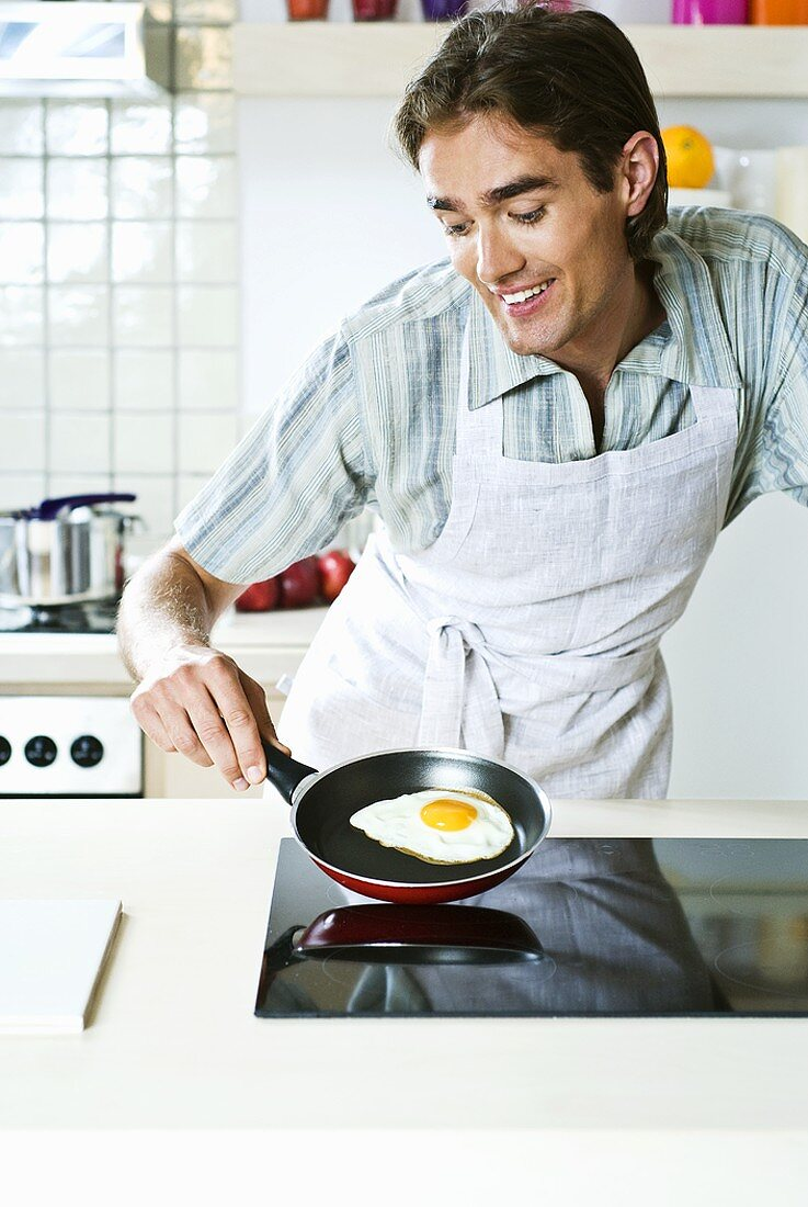 Young man frying an egg on hob