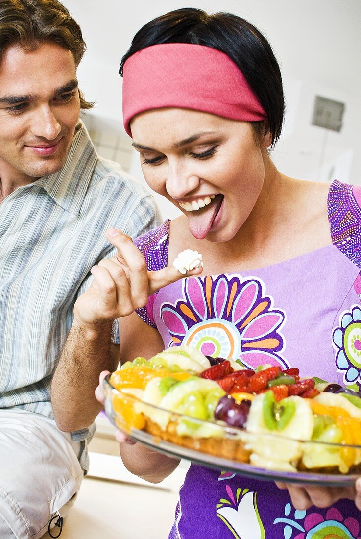 Woman with fruit tart licking cream from a man's finger