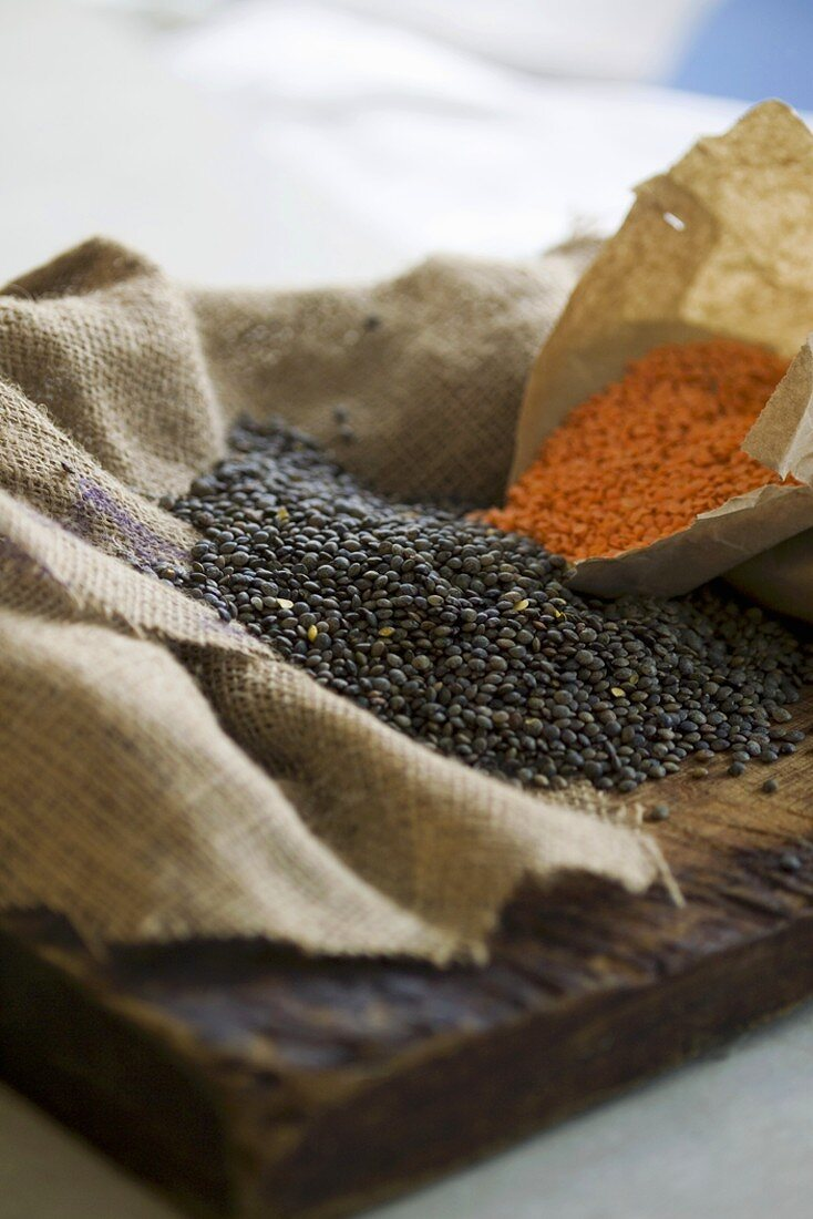 Red and black lentils on jute and wood