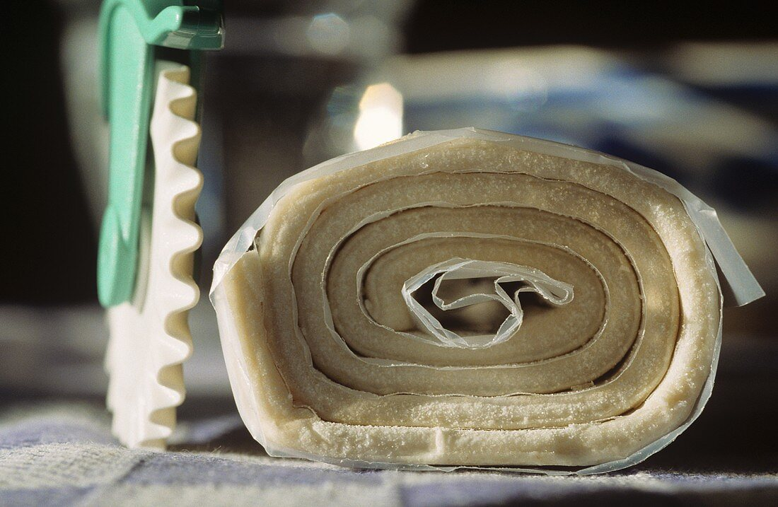 Raw puff pastry (rolled up with plastic food wrap)