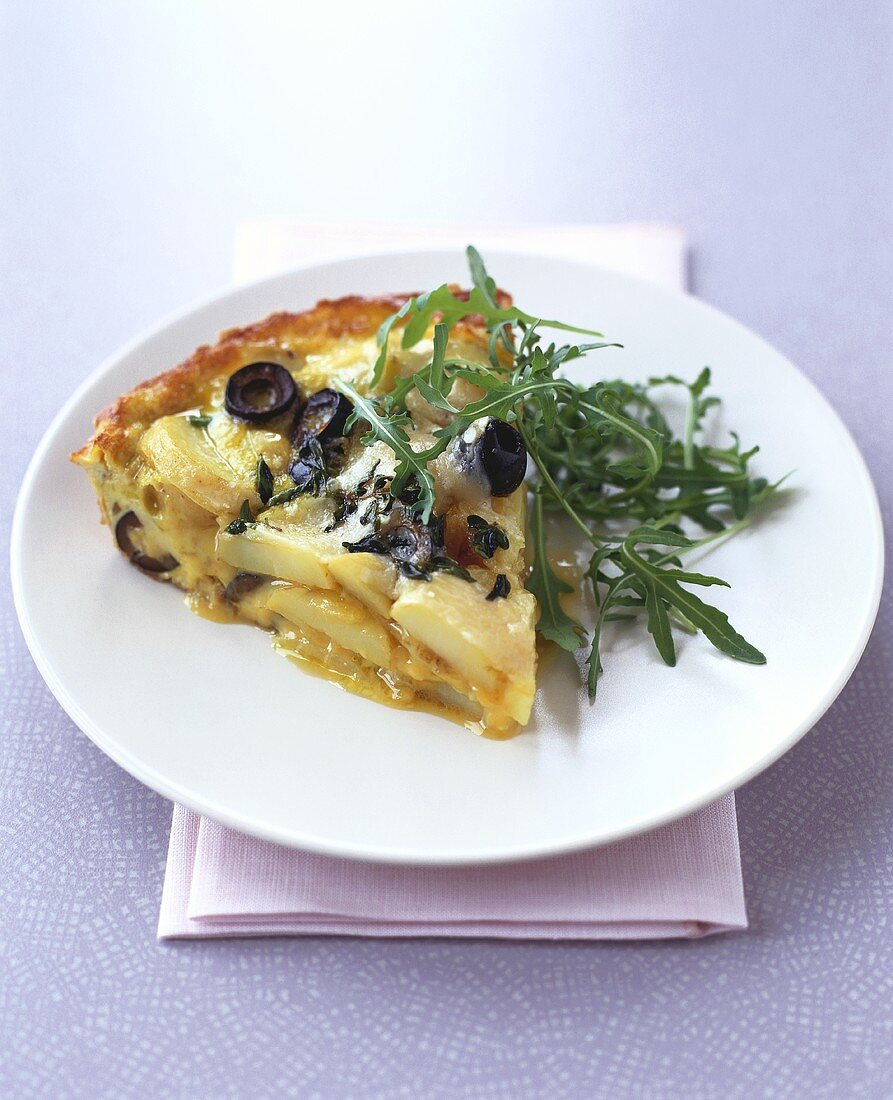 A piece of tortilla with olives and rocket