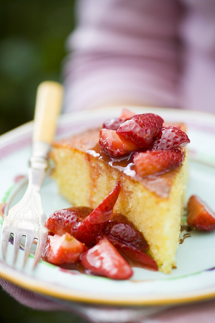 A piece of orange cake with fresh strawberries