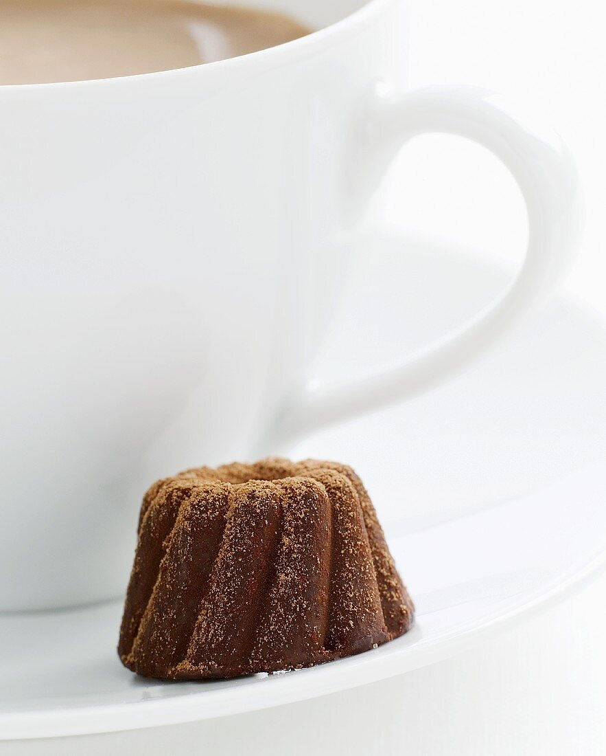 Gugelhupf chocolate in the saucer of a cup of coffee