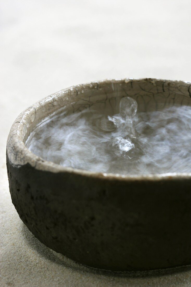 Drop of water falling into a stoneware bowl of water