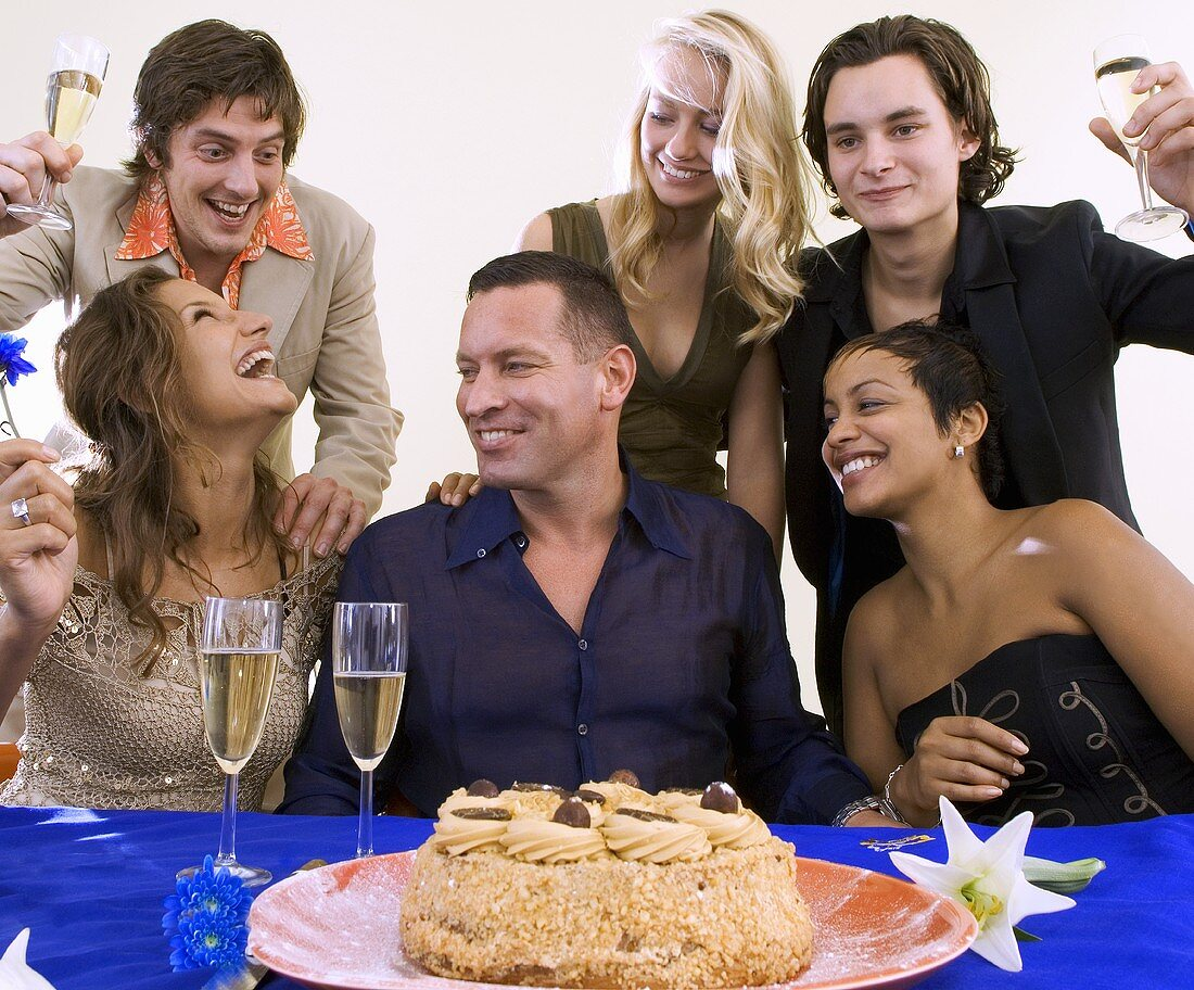 People celebrating with cake and sparkling wine