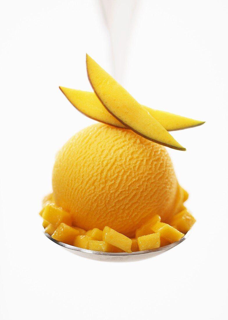 Mango sorbet with fresh fruit on a spoon