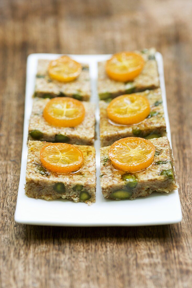 Six pistachio & almond squares with kumquats on a platter