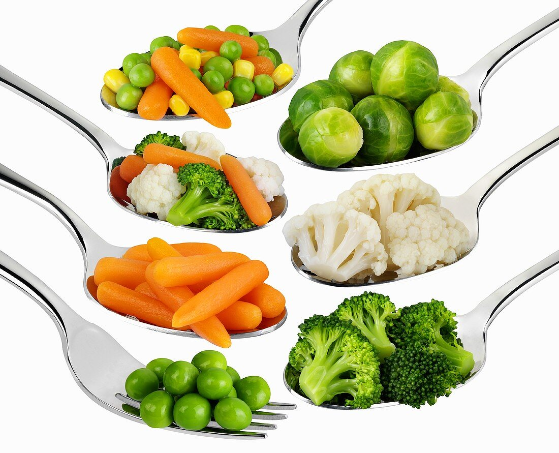 Various vegetables on spoons and forks