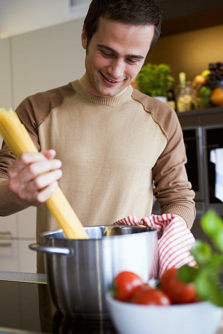 Young man putting spaghetti into a pan