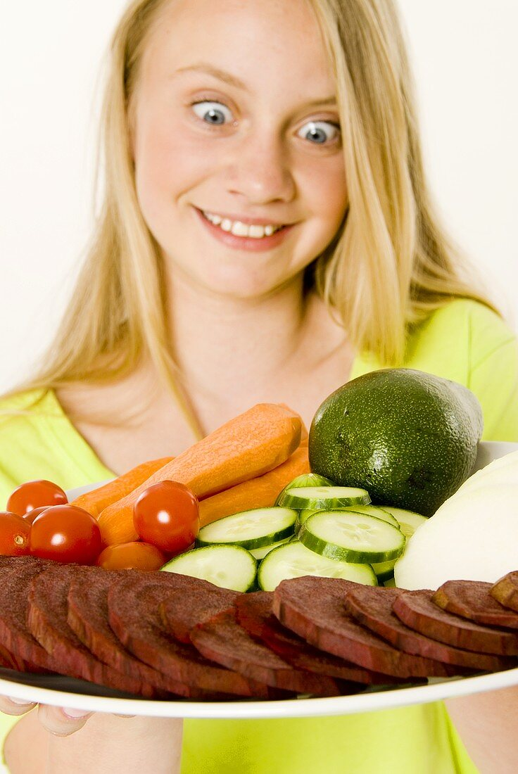 Young girl looking at plate of vegetables