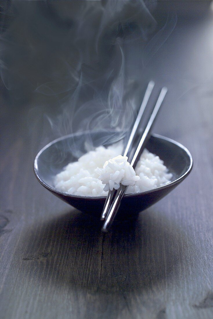 Cooked rice in small bowl with chopsticks